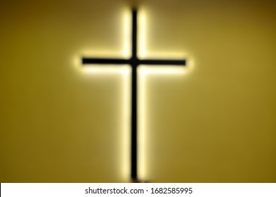 lonely cross with backlight in yellow wall