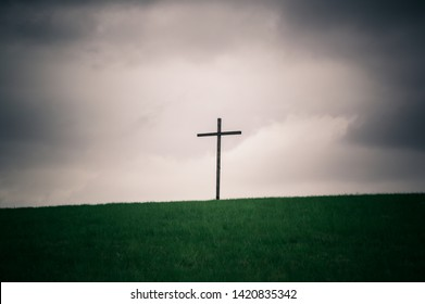 Lonely cross series. A wooden cross on a hilltop horizon background with heavy sky. Symbol of Christianity. Plenty of copy space.
