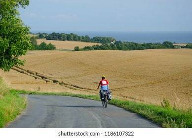 Lonely cycle tourist on the scenic countryside road in Denmark - island Mon (near Busene).