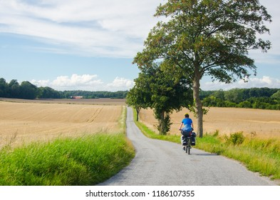 Lonely cycle tourist on the scenic countryside road in Denmark - island Mon.