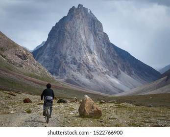 Lonely cyclist man riding in between rocks in Himalayan mountains, with the big Holy Mountain Gomburanjon in background - Lakang Sumdo, Ladakh, India