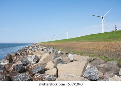Lonely cyclist riding at an endless dike with windmills in the Netherlands