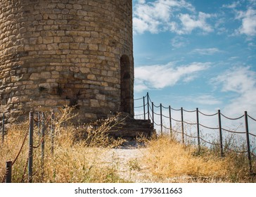 Lonely defense tower. Stone imposing circular tower. Vintge mood. Autumn landscape.