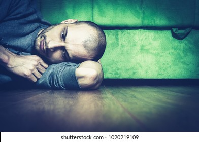 Lonely and depressed anxious man lying on the floor of his home feeling desperate miserable and sad