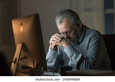 Lonely depressed senior man connecting at night with his computer and looking down: he feels confused, sad and lonely