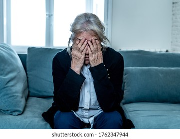 Lonely depressed senior old widow woman crying on couch in isolation at home, feeling sad and worried missing husband and family in COVID-19 Outbreak, lockdown, social distancing and Mental health.