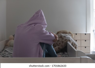 Lonely depressed teen school child girl wearing hood crying sitting alone on bed. Sad misunderstood abused adolescent introvert teenager feeling hurt. Teenage psychology and puberty problems concept