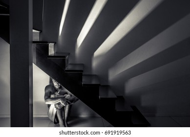 Lonely and depressive man staying under stair, black and white photography with strong shadows, schizophrenia, depression, phobia, insanity