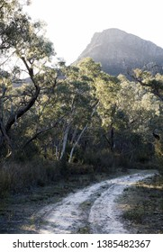 A lonely dirt road around the bend towards the large mountains of the Grampians National park during sunset.