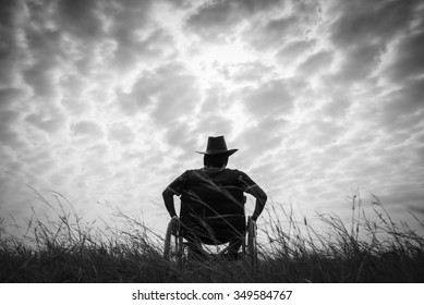 Lonely disabled man in wheelchair at black background