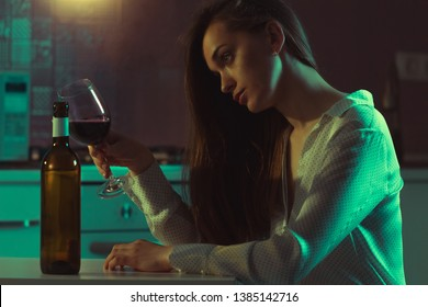 Lonely, divorced beautiful young woman with alcoholic beverage is drinking alone in evening at home. Female alcoholism and alcohol addiction. Life difficulties and problems