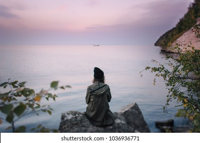 Lonely dreamy girl in a black hat and a dark cloak that sits on a large rock and looks at a ship floating in the distance