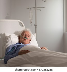Lonely elder patient on a drip in hospital