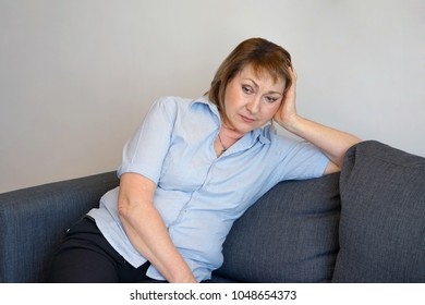 A lonely elderly woman is sitting on the sofa at home. She is depressed and separated from problems in her personal life. The concept of loneliness and loss of love.