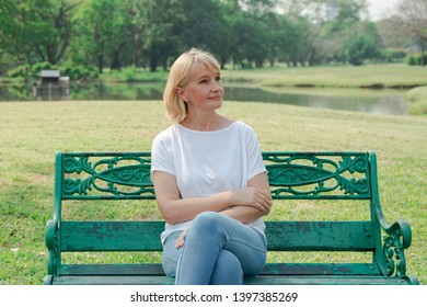 Lonely elderly woman sitting on a bench in a city park background