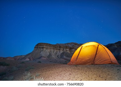 Lonely evening camping in Mongolian canyons. yellow illuminated tent is located near canyons