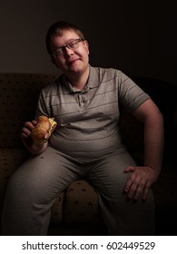Lonely fat guy eating hamburger. Bad eating habits.