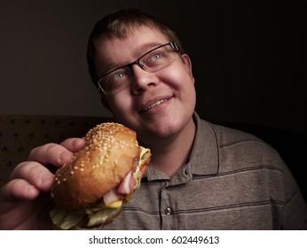 Lonely fat guy eating hamburger. Bad eating habits. Closeup.