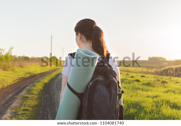 Lonely female tourist walking by the empty endless road. Concept of the vacation, travel, journey, backpacking, hiking, loneliness.