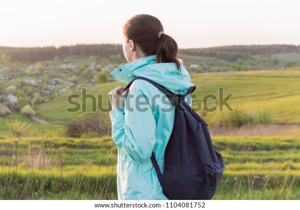 Lonely female traveller in blue outerwear and with dark blue backpack standing on the hill covered with the grass. Concept of the vacation, travel, journey, backpacking, hiking, loneliness.