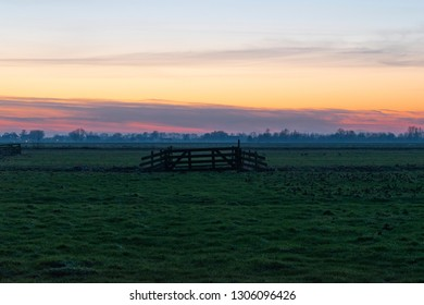 Lonely fence in the middle of a meadow. Sunset in the Green Heart of the Netherlands, Europe.