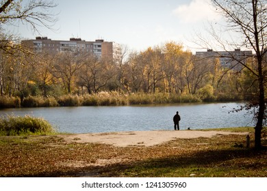 lonely figure on the shore of the pond in late autumn
