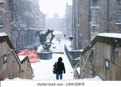 A lonely figure walking amidst heavy snowfall in the city of Edinburgh in the deafeningly quiet empty street.