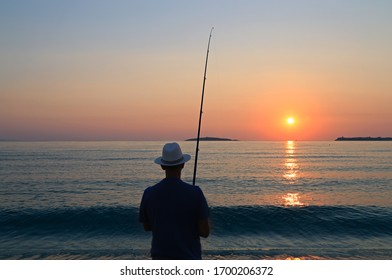 Lonely fisherman with hat on the sea shore at sunrise