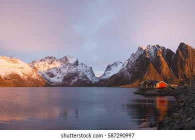 Lonely fisherman house with alight window under the mountain. Photo made in February near the town of Reine, Lofoten islands
