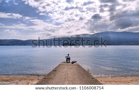 lonely fisherman on dock on Lake Maggiore with blue water and cloudy sky and rays of light in Verbania, Italy