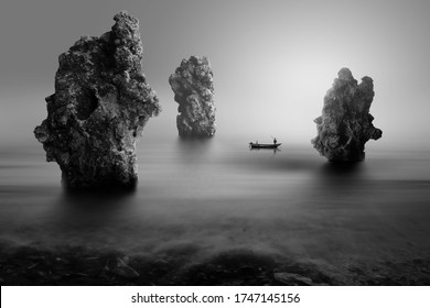 lonely fisherman on the stone beach, black and white photography