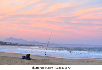A lonely fisherman is sitting and relaxing at the Kleinbrak  beach checking his mobile for messages with his line in the cold winter waters.