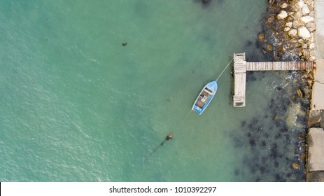 Lonely fishing boat and wooden pier in turquoise ocean, sea. Aerial photo, top view