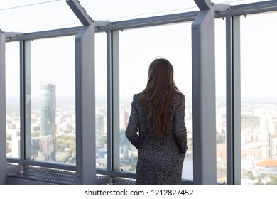 lonely girl in an autumn coat back and looks into the distance on the roof with a panoramic view of the city