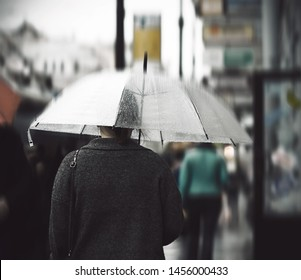 A lonely girl in a gray sweater under a transparent umbrella goes under a heavy rain through the city crowd and the grayness of autumn everyday life.