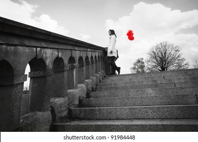 lonely girl with heart-shaped balloons in park
