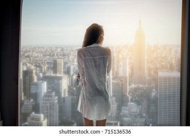 A lonely girl in the high floor of the building is looking to the city out side at sunrise time.