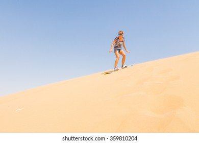 Lonely girl learning to sand boarding in a desert down the dunes