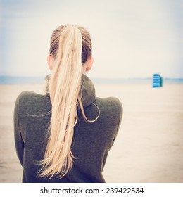 Lonely girl with long blond ponytail at empty foggy beach. Selective focus. Image with filter effect instagram
