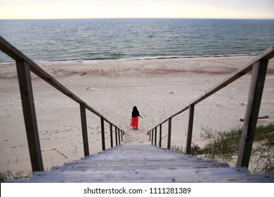 A lonely girl in a long dress is walking along the seashore. Desert, sand, horizon. Lithuania, Nida, Europe. The Curonian Spit. Walk along the beach and dunes.