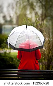 Lonely girl in a park in a rainy day with umbrella