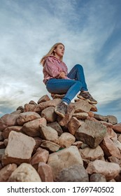 A lonely girl sits on a mountain of rocks