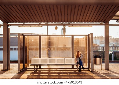 Lonely girl sits on the steel bench waiting for someone