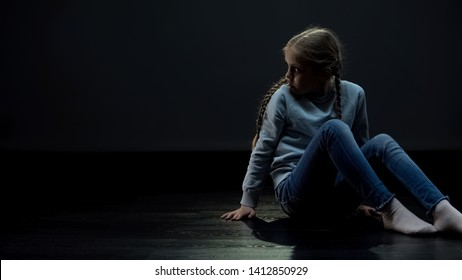 Lonely girl sitting in dark room and looking around, orphan waiting family