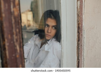 Lonely girl sitting near the window thinking about something. Portrait of a beautiful young sad girl looking out the window.