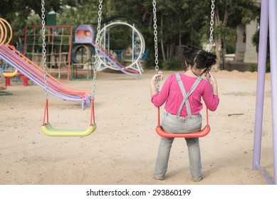 Lonely girl sitting on chain swing in the park