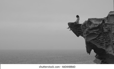 A lonely girl sitting on the cliff edge at the mist ocean and looking out for something in black and white tone