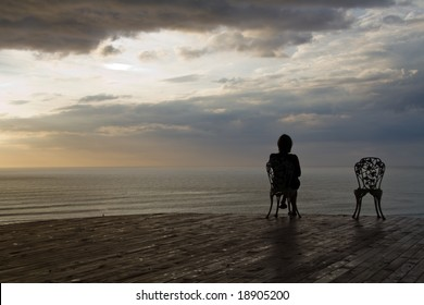 lonely girl sitting on an old chair and watching the sunset