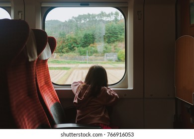 A lonely girl sitting at window seat looking out of the train