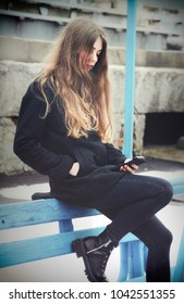 Lonely girl with smartphone sitting on the bench